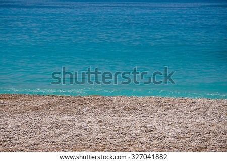 pebble beach washed by the turquoise sea water - stock photo