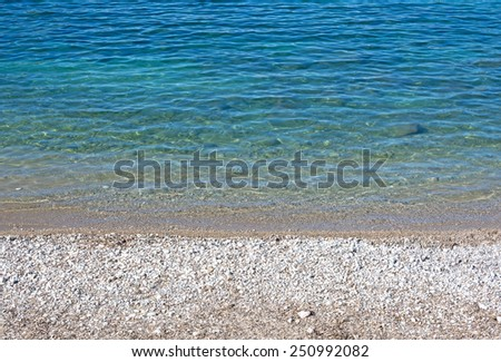 Pebble beach with clear ultramarine and turquoise water in Port de Soller - stock photo