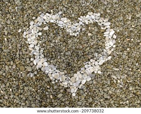 Pebble heart on the beach. - stock photo