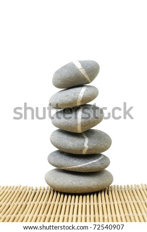 Pebble stones on on bamboo stick straw mat - stock photo