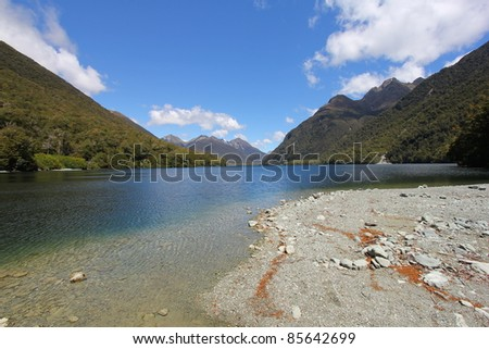 Pebbles along a clear river on a cloudy day - stock photo