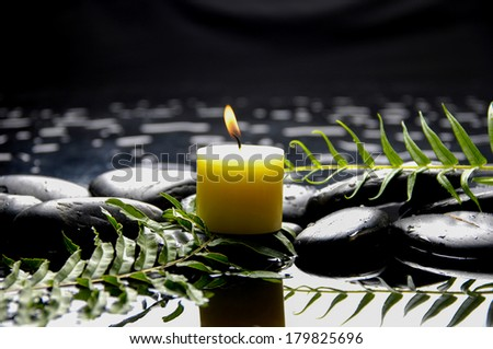 pebbles and candle ,leaf on wet background