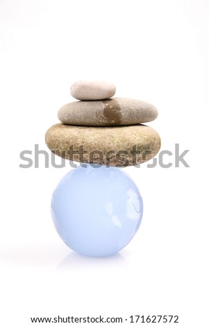 pebbles balancing on a glass globe as a symbol for world in balance - stock photo