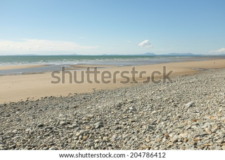 Pebbles lead down to a deserted sandy beach and sea with mountains in the distance.