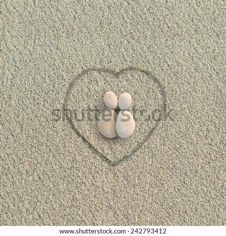Pebbles shapes lovers with heart on the sand - stock photo