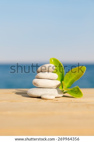 Pebbles stack and leafs on the wood pier balance over sea - stock photo