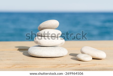 Pebbles stack on the wood pier balance over sea
