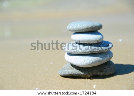 Pebbles stacked on a sandy beach