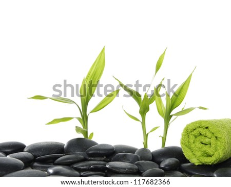 Pebbles stones with green towel and bamboo leaf