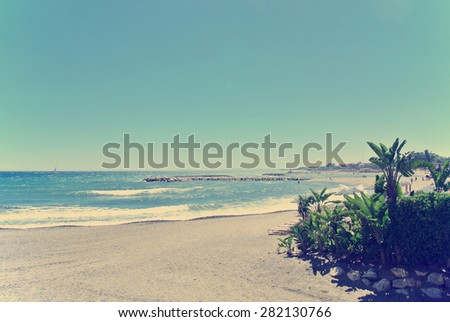 Pebbly beach in Spanish luxurious seaside resort Puerto Banus, close to Marbella, on a sunny summer day. Filtered image in faded, washed-out, retro style; summer travel vintage concept. - stock photo