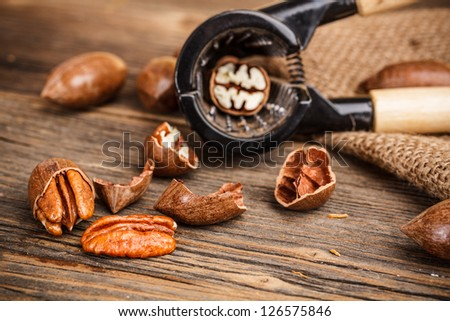 Pecan nut in nutcracker on rustic wooden background - stock photo