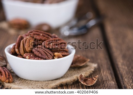 Pecan Nuts (selective focus) on an old vintage wooden table - stock photo