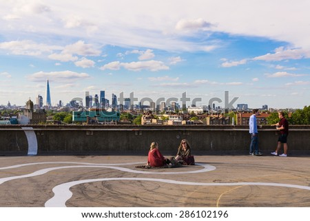 Peckham, London, UK - June 06 2015: Two girls and two guys drinking beer on the floor of a rooftop bar cafe in south-east London.View of the City of London skyscrapers and the Shard in the background. - stock photo