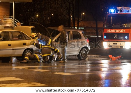 PECS, HUNGARY - DEC. 01: Firefighters try to help the victim of car accident on Dec. 01, 2010 on Road 6 in Pecs, Hungary. - stock photo