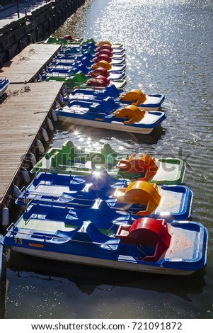 Pedal boat in a row near pier with sun flares in Klaipeda, Lithuania