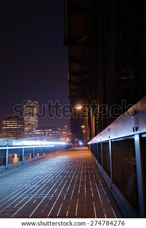 Pedestrian and bicycle path that is part of the metal transport truss bridge over Willamette River in Portland in twinkling night lights high-rise office buildings cyclist headlight on truss bridge. - stock photo