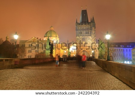 Pedestrian area on the Charles bridge and distant towers and church domes surrounded by fog at night, Prague, Czech Republic - stock photo