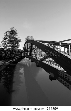 Pedestrian Bridge Casts Shadow in Water - stock photo