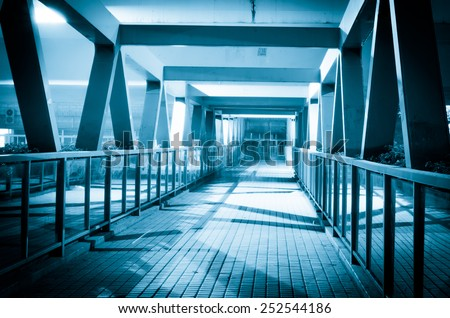 pedestrian bridge in guangzhou, China, at night, and walking business people in motion blur - stock photo