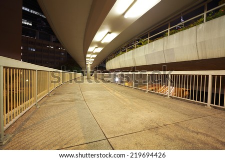 Pedestrian bridge perspective  long corridor of night - stock photo