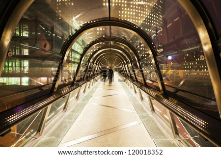 pedestrian bridge with glass dome in La Defense, Paris, at night, and walking business people in motion blur - stock photo