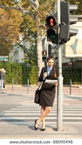 pedestrian businesswoman reading the newspaper next the traffic light - stock photo