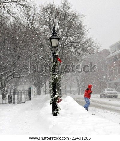 Pedestrian crossing main street during a  New England snow storm