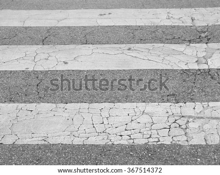 Pedestrian crossing marking on old damaged asphalt road - stock photo