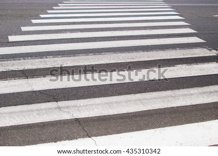 Pedestrian crossing on the road in the form of a zebra - stock photo