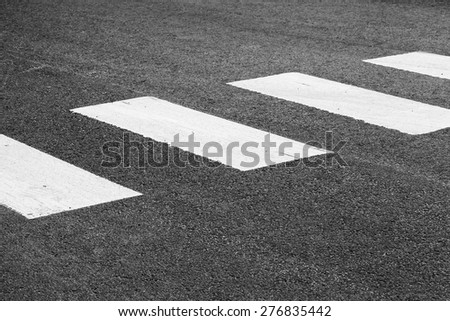 Pedestrian crossing road marking, white rectangles over gray asphalt pavement, selective focus and shallow DOF - stock photo