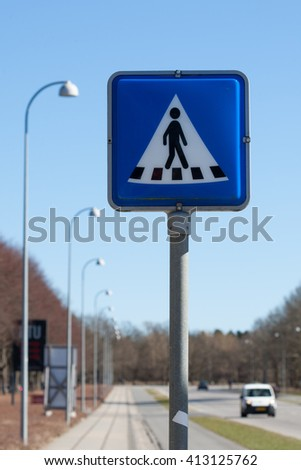 pedestrian crossing sign with car blurred in background - stock photo