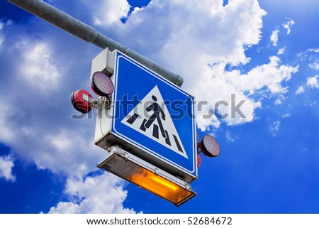 Pedestrian crossing sign with light against  the blue sky with some clouds - stock photo