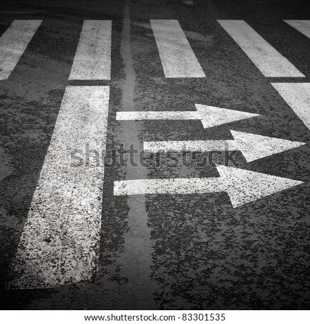 Pedestrian crossing with road marking: white arrows and rectangles on the dark asphalt road. - stock photo