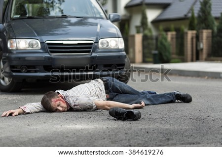 Pedestrian hit by a car lying on the street - stock photo
