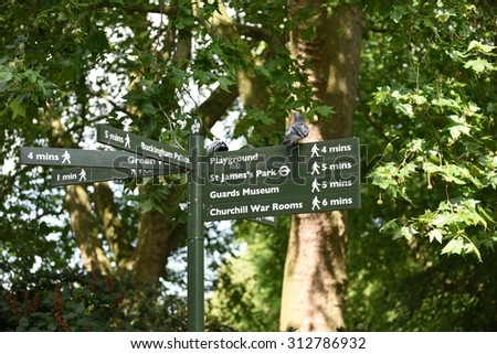 Pedestrian signposts in London's St. James's Park with green natural backdrop - stock photo