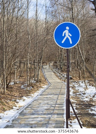 Pedestrian walking lane walkway footpath road sign on pole post, large blue round  route traffic roadside signage - stock photo