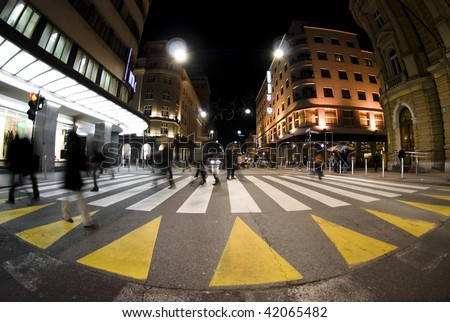 Pedestrian zebra crossing on busy street at night