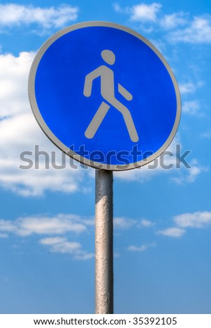 pedestrian zone sign against blue sky with clouds