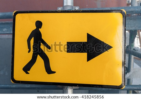 Pedestrians bypass direction. Yellow road sign on construction site border - stock photo