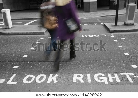 Pedestrians crossing the road, look sign over asphalt in London - stock photo
