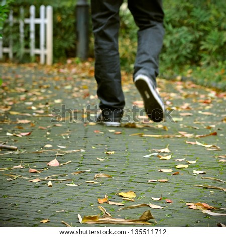 Pedestrians walk in the fallen leaves of the road - stock photo