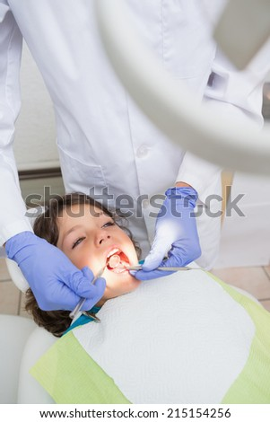 Pediatric dentist examining a little boys teeth in the dentists chair at the dental clinic - stock photo