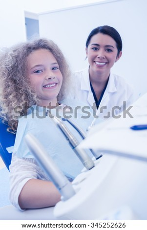 Pediatric dentist smiling with little girl in the chair at the dental clinic - stock photo