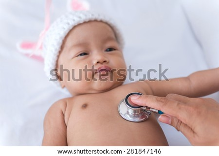 Pediatric doctor exams newborn baby girl with stethoscope in hospital. - stock photo