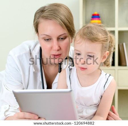 Pediatrician and little girl using tablet computer - stock photo