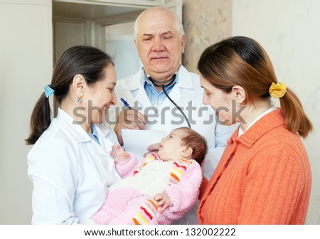 pediatrician doctors give the healthy baby to happy mother - stock photo