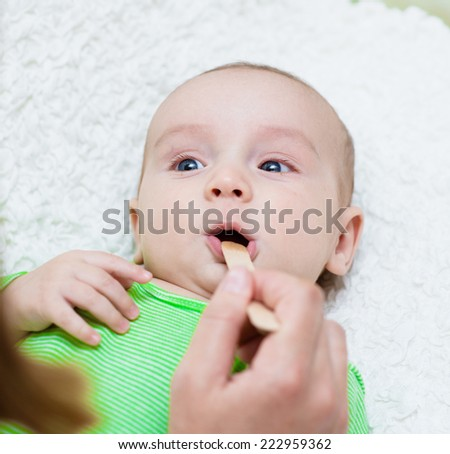 pediatrician examines a newborn baby with a spatula - stock photo