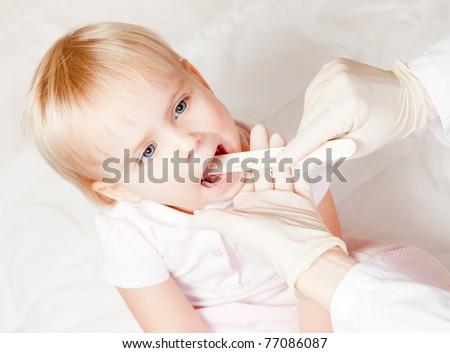 Pediatrician examining little girl's throat with tongue depressor - stock photo