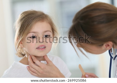 Pediatrician in office checking on child's throat - stock photo