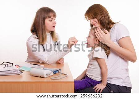 Pediatrician looking into the throat of the child sitting on the lap of mother - stock photo